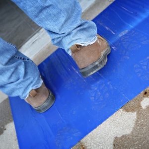 man stepping on blue dirt trapper
